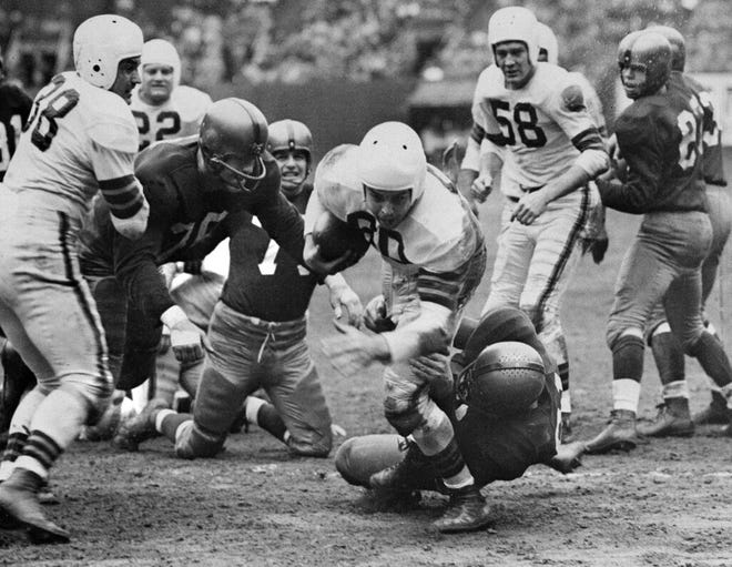 Browns quarterback Otto Graham is stopped short of the goal line by Gene Pepper of Washington in the second quarter in Cleveland, Nov. 20, 1950.  Cleveland players also in the play Weldon Humble (38), Frank Gatski (22), and Mac Speedie (58), while the other Washington players are Paul Lipscomb (76) and Jerry Houghton (71).  The Browns won, 20-14.  (AP Photo/Julian C. Wilson)