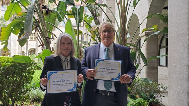 St. Augustine Vice Mayor Nancy Sikes-Kline and City Manager John Regan stand in the courtyard at City Hall with their Home Rule Hero awards in hand from the Florida League of Cities.