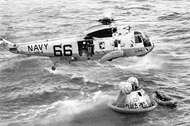 In this July 24, 1969, photo from the U.S. Navy, Navy UDT swimmer Clancy Hatleberg prepares to jump from a helicopter into the water next to the Apollo 11 capsule after it splashed down in the Pacific Ocean, to assist the astronauts into the raft at right.