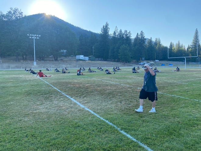 Players stretch on the first day of football camp in Etna in July of 2021.