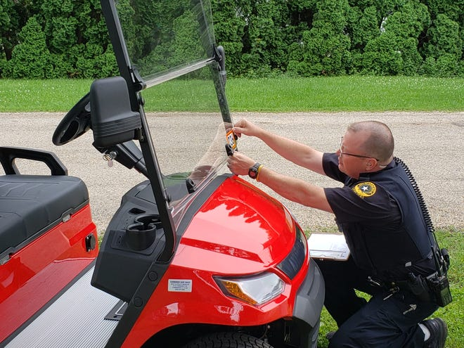 Kewanee Police Officer Tim Bryner affixes a registration tag to a golf cart after completing a slow-moving vehicle inspection. Last month, the Kewanee City Council approved an ordinance that allows residents to operate golf carts and off-highway vehicles on most streets in Kewanee.