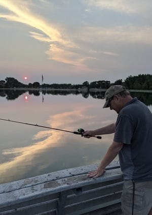 With the Monday evening sky and sunset reflecting off of Lake Minne-Eho at Wylie Park, George P. Sullivan of Aberdeen tries to snag a fish from a small dock on the east side of the lake.