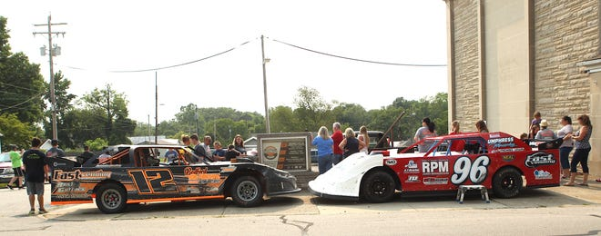 A crowd gathers around Tommy East's Super Stock, (left), and the #96, which is driven by Grant Simpson. Simpson is the Grandson of local racing legend Kenny Simpson, and this car is painted to replicate the last car that Kenny Simpson raced in.