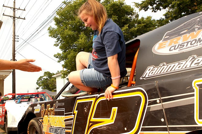 Chloe Gilliland climbs out of Tommy East's Super Stock Monday afternoon at Momentum Community Church. The church kicked off their Vacation Bible School week (themed Racing to Jesus), with several local race drivers bringing their cars to the church parking lot for the kids look at. East is a local driver who races at Brownstown Speedway.