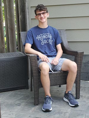 Colin Jaeger chills in his backyard in his Great Plains Lutheran Honor Society t-shirt