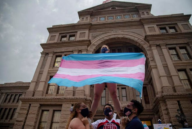 Ali Cross of the Austin Cheer squad waved a trans flag in April while her teammates held her up on the steps of the state Capitol at a rally against anti-trans legislation.
