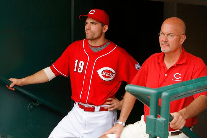 Reds medical director Dr. Tim Kremchek stands in the dugout tunnel at Great American Ball Park with first baseman Joey Votto
