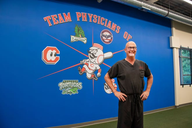 Reds medical director Dr. Tim Kremchek stands in front of logos of the Reds affiliates at the Beacon Orthopaedics Complex at Summit Woods