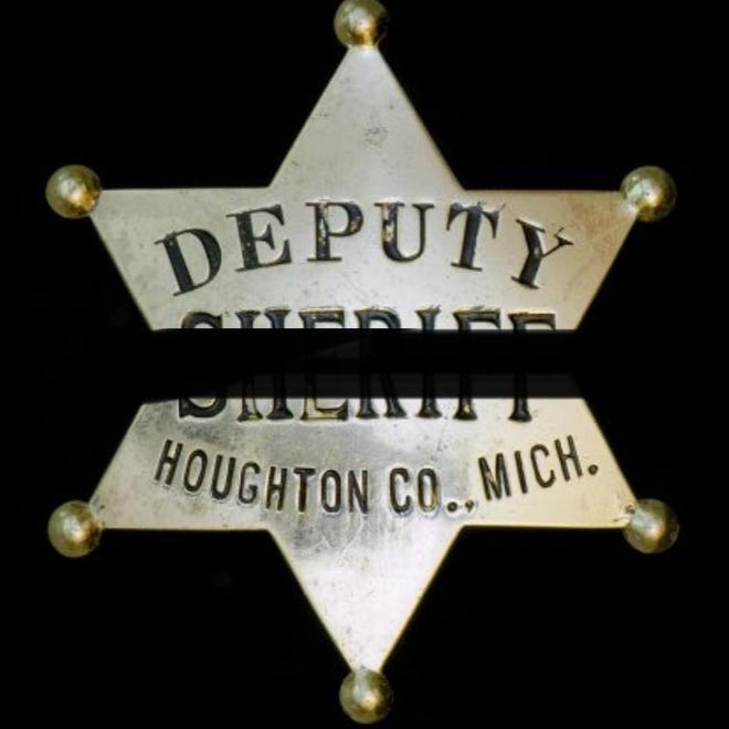 A black line goes across the middle of a badge from the Houghton County Sheriff's Office, a symbol of mourning for a fallen police officer.