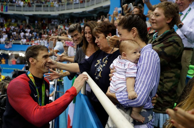 FILE - In this Tuesday, Aug. 9, 2016, file photo, United States' Michael Phelps celebrates winning his gold medal in the men's 200-meter butterfly with his mother Debbie, fiance Nicole Johnson and baby Boomer during the swimming competitions at the 2016 Summer Olympics in Rio de Janeiro, Brazil.