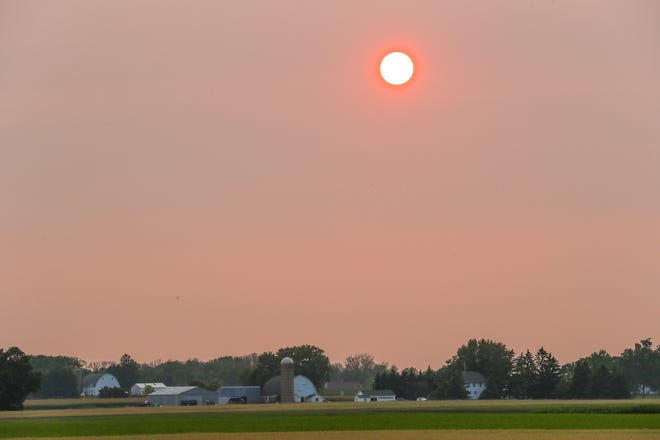 The sun sets behind a farmstead Monday, July 19, 2021, near State 44 outside of Oshkosh. Smoke from wildfires in Canada is creating hazy conditions over Wisconsin.