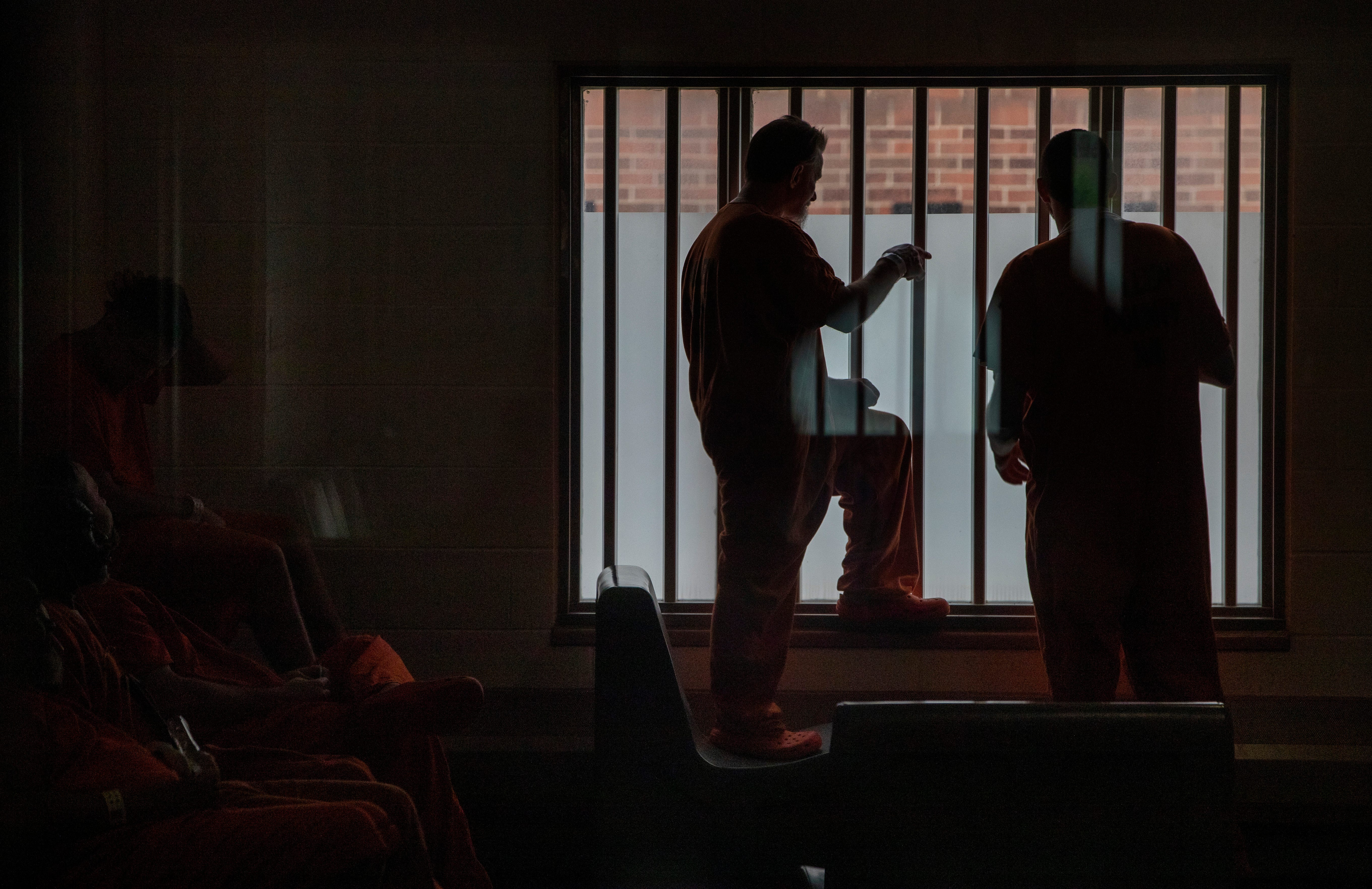 Detainees stand near a window Thursday, June 24, 2021, at the Allen County Jail in downtown Ft. Wayne, Ind.