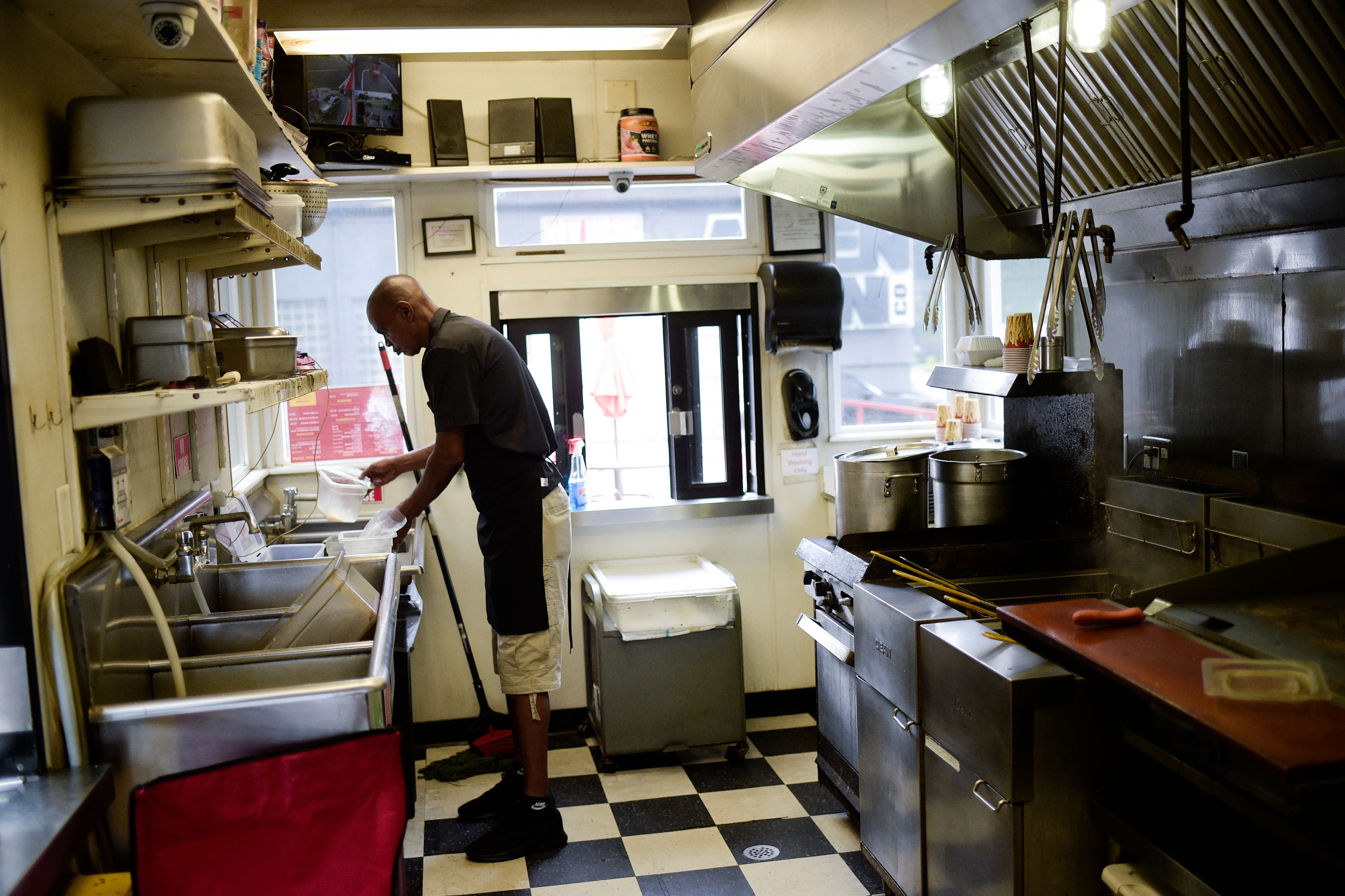 The Burger Boys building on Chapman Highway is barely big enough for two people, but that's all the space Andre Bryant needs. He has a potato cutter on the wall, two small deep fryers, a single grill and a burger-making station complete with his fresh toppings for the day.