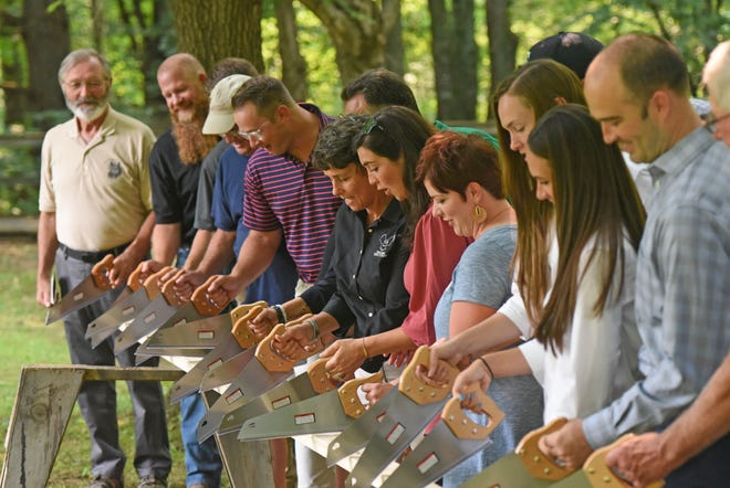 Officials cut a piece of wood instead of a ribbon on Monday to celebrate the start of construction on a $380,000 treehouse classroom project at the Ohio Bird Sanctuary.