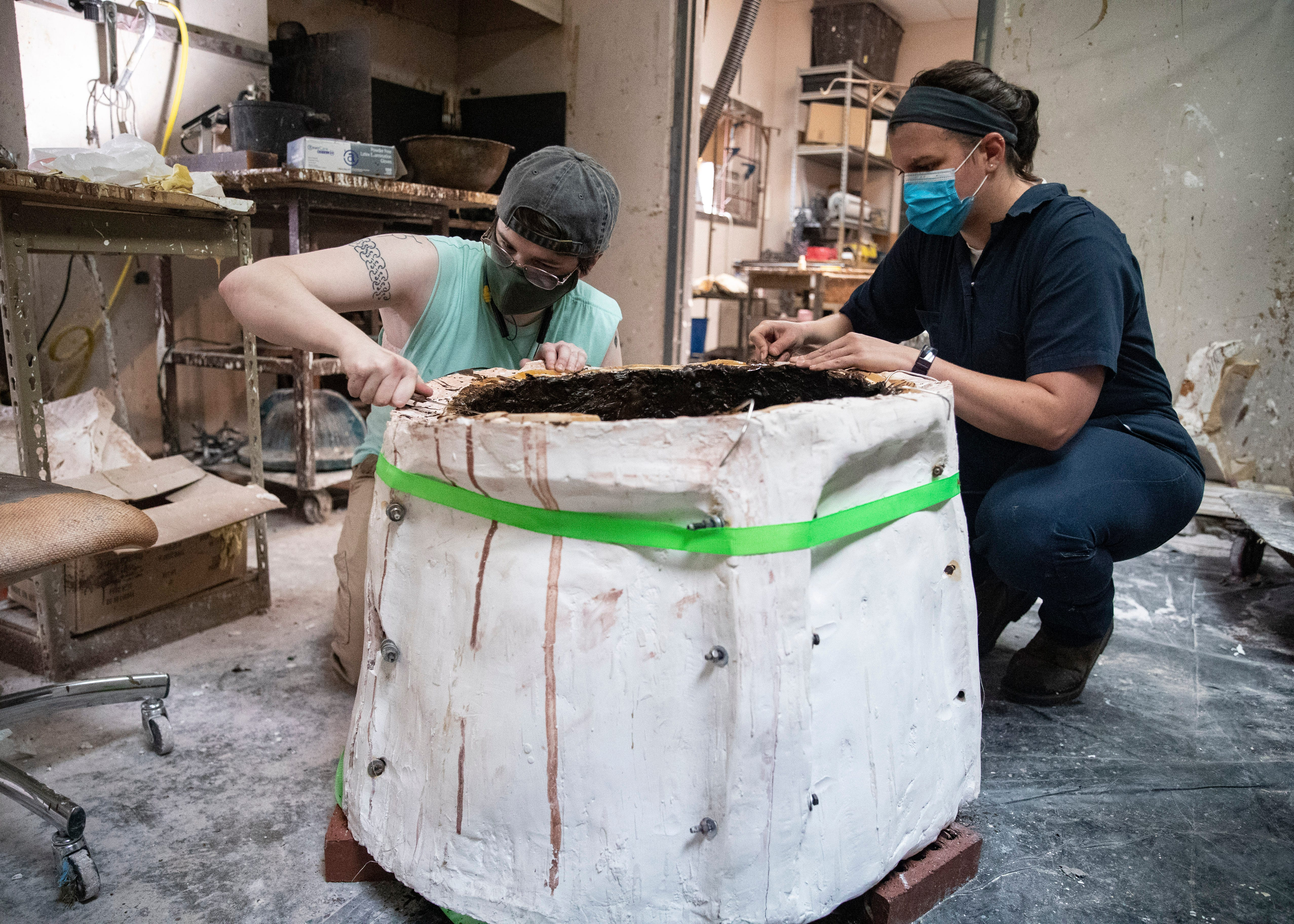 Artisans Emily Hogan and Marda Mesler during the mold making process to create the statue of Ida B. Wells, the African American civil rights advocate and journalist who fought against racism, segregation and lynching, at the Lugar Bronze Foundry in Eads, Tenn., on Tuesday, June 8, 2021.