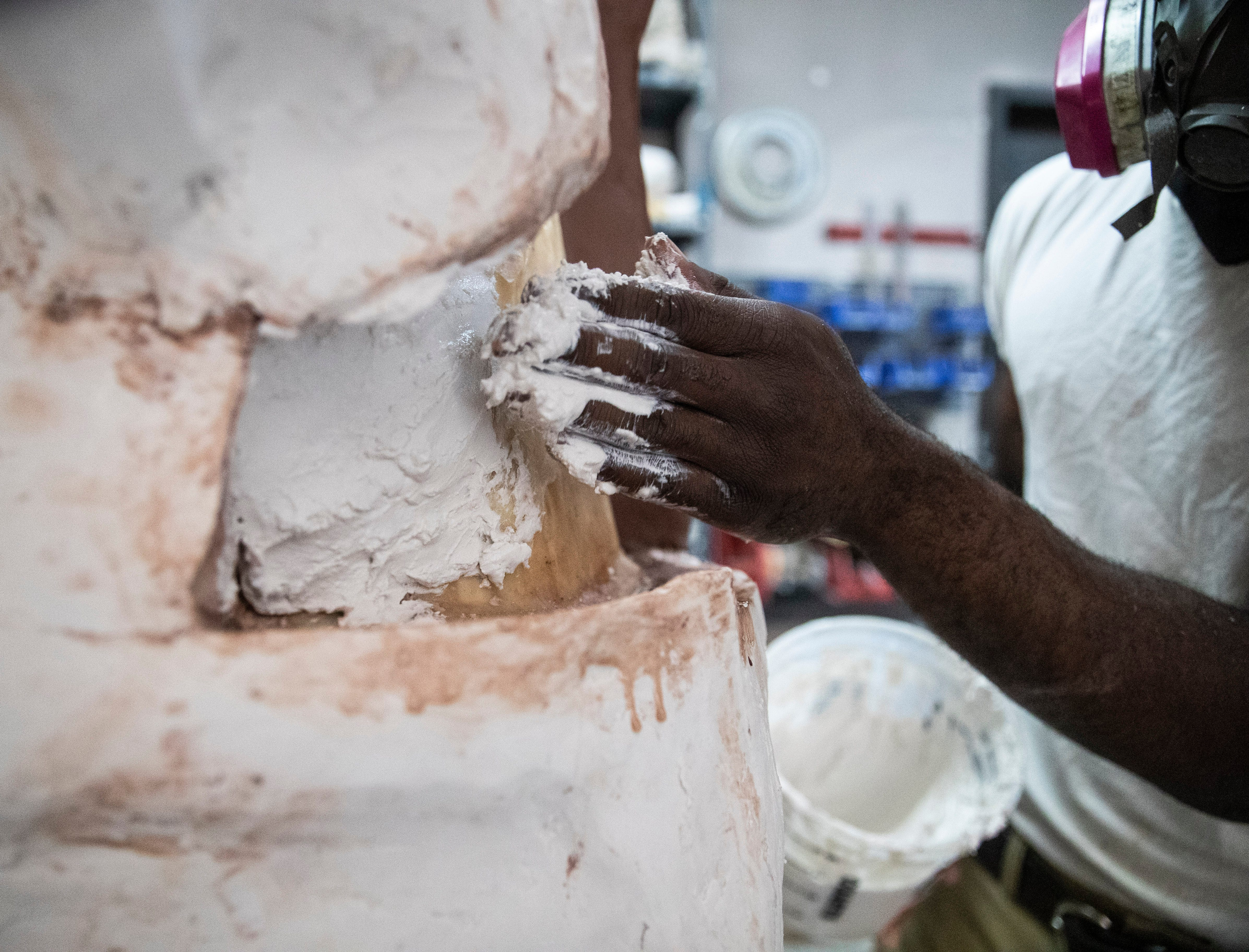The team uses a two-part liquid rubber to cover the entire clay statue. Because the rubber is flexible, they make a plaster to cover the rubber.