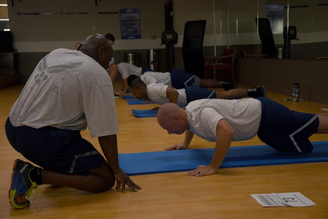 Members from the 908th Airlift Wing at Maxwell Air Force Base perform the push-up portion of the Physical Fitness Assessment test.