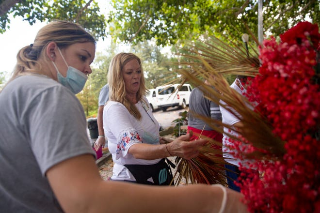 """David Lawrence Center Executive Director's Assistant, Kim Elsworth, center, works with residents in the Crossroads Addiction Recovery program to create the """"Phoenix Rising"""" floral arrangement, Friday, July 16, 2021, at the David Lawrence Center in North Naples."""