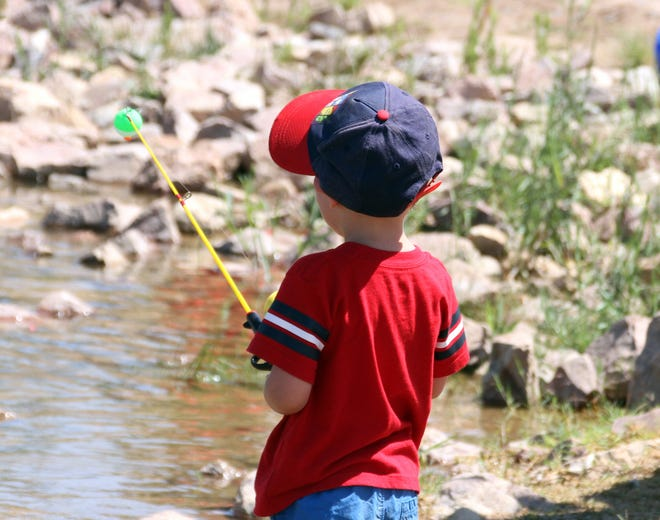 Ezra Pena, 3, waits for a bite during Saturday's free fishing day for kids at Trees Lake.
