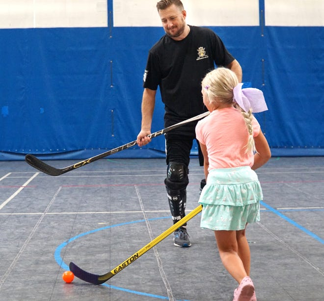 Brandon McCullough plays some ball hockey with his daughter Harper, 7, at the Livonia Recreation Center on July 20, 2021.