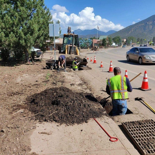 People work to clear debris from drains and roadways after flooding in Coconino County.
