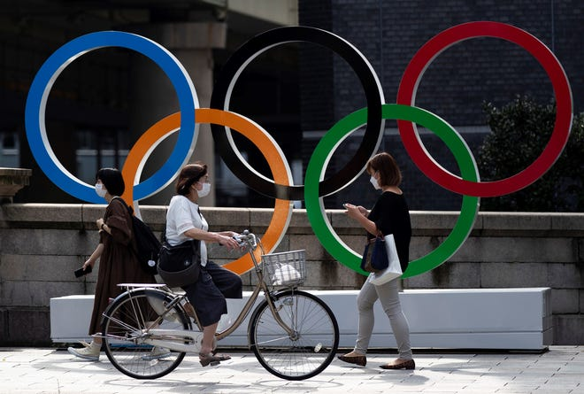 In this July 15, 2021, file photo, people walk by the Olympic rings installed by the Nippon Bashi bridge in Tokyo. The Tokyo Summer Games will likely go on, despite a state of emergency existing in Japan because of a surge in COVID-19 cases.