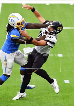 Jacksonville Jaguars quarterback Gardner Minshew II (15) gets hit by Los Angeles Chargers defensive end Melvin Ingram (54) while throwing a pass, Sunday, October 25, 2020 in Inglewood, Calif. The Chargers defeated the Jaguars 39-29. (John Cordes/AP Images for Panini)