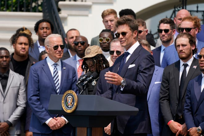 President Joe Biden, surrounded by members of the Tampa Bay Buccaneers, listens as Tampa Bay Buccaneers quarterback Tom Brady speaks during a ceremony on the South Lawn of the White House, in Washington, Tuesday, July 20, 2021, where Biden honored the Super Bowl Champion Tampa Bay Buccaneers for their Super Bowl LV victory. (AP Photo/Manuel Balce Ceneta)