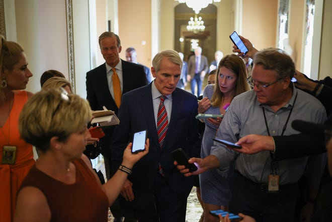 Sen. Rob Portman, R-Ohio, right, and Sen. John Thune, R-S.D., are surrounded by reporters outside the Senate Chambers on July 19, 2021 in Washington, D.C.
