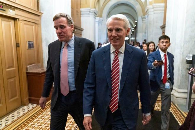 Sen. Mark Warner, D-Va., left, accompanied by Sen. Rob Portman, R-Ohio, walk for closed door talks about infrastructure on Capitol Hill in Washington July 15.
