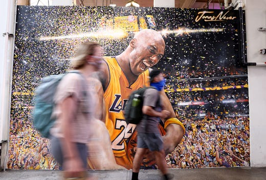 People wear face coverings while walking by a Kobe Bryant mural by Jonas Never in Grand Central Market on July 19, 2021 in Los Angeles.