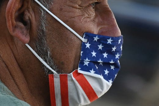 """A man wears an American flag face mask on July 19, 2021 on a street in Los Angeles on the second day of the return of the indoor mask mandate in Los Angeles County due to a spike in coronavirus cases. The US surgeon general on July 18 defended a renewed mask mandate in Los Angeles, saying other areas may have to follow and adding that he is """"deeply concerned"""" about the Covid-19 outlook in the fall. LA County reported another 1,233 Covid-19 cases, the 11th consecutive day the number has topped 1,000."""