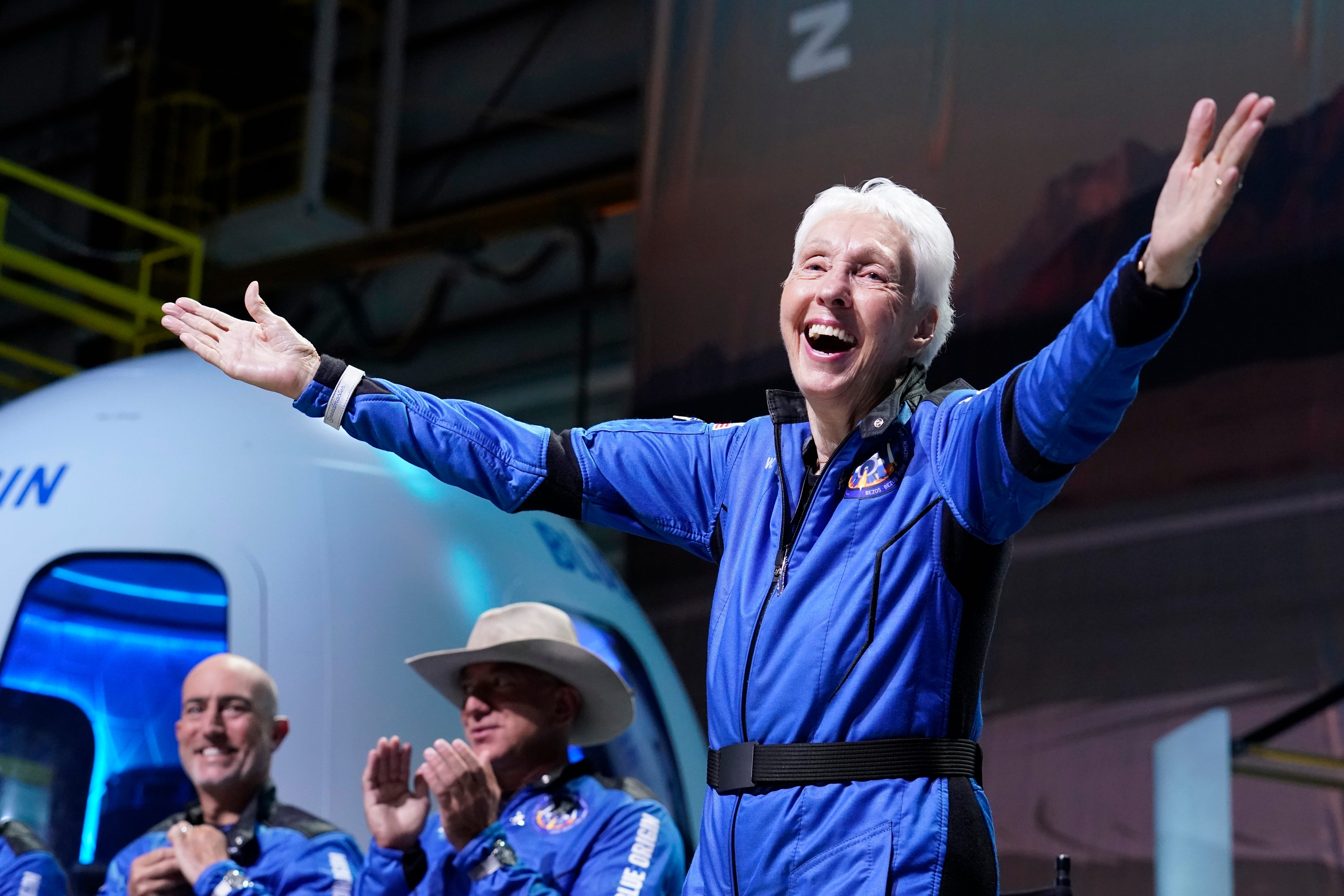 Wally Funk lifts her arms as she describes her experience aboard the Blue Origin.