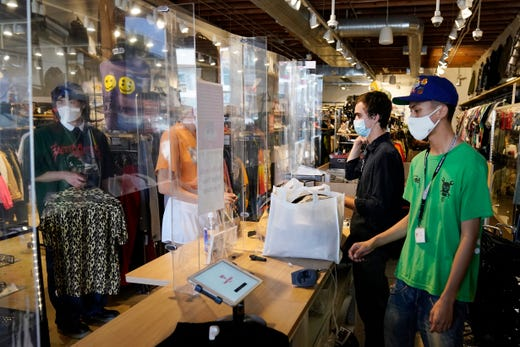 Employees check out customers at 2nd Street second hand store Monday, July 19, 2021, in the Fairfax district of Los Angeles. Los Angeles County has reinstated an indoor mask mandate due to rising COVID-19 cases.