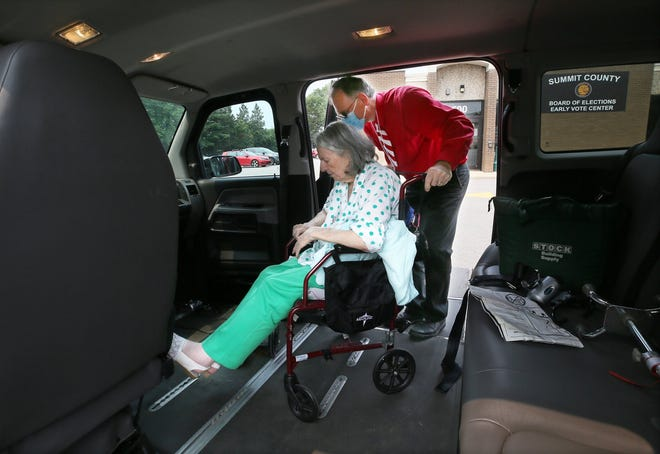 Michael Substelny, a volunteer driver for RideShare2Vote, gets Barbara Stewart, 84 back to his van after she voted Tuesday  at the Summit County Board of Elections Early Vote Center in Akron.
