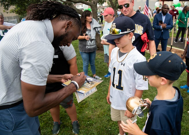 New York Jets running back and Central Bucks South alum Josh Adams, left, signs autographs for John Logan, 13, center, of Collegeville, and his brother, Brendan Logan, 9, following a groundbreaking ceremony at DocterAdams Community Park in Warrington on Wednesday.