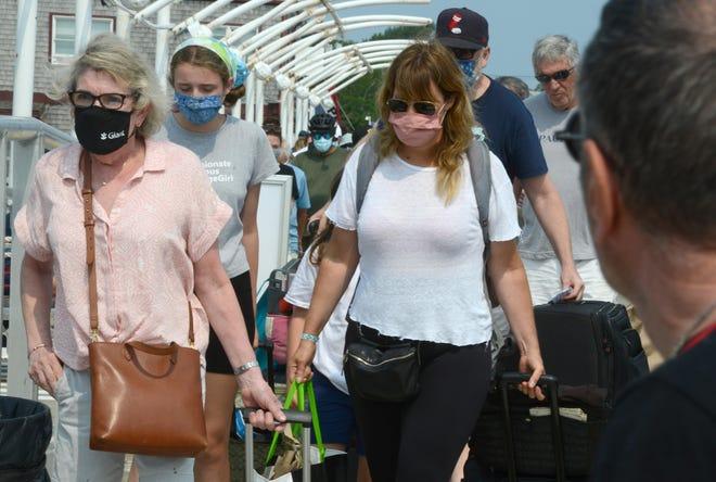 Những hành khách đeo mặt nạ sẽ đi đến chuyến phà nhanh đã kết thúc ở Boston trên MacMillan Wharf ở Provincetown trong tuần này.