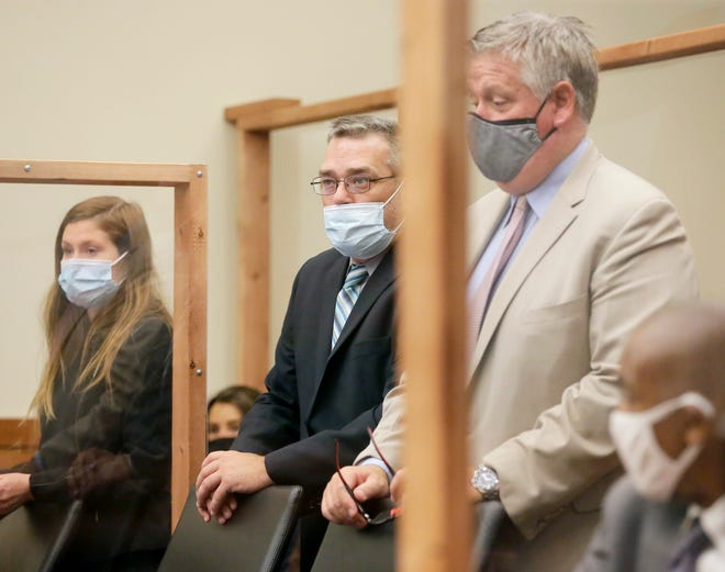 Former Columbus Police Officer Adam Coy, center, stands between defense attorneys Kaitlyn Stephens and Mark Collins in Franklin County Common Pleas Court during a status hearing Wednesday regarding his murder case in the shooting death of Andre Hill, an unarmed Black man.
