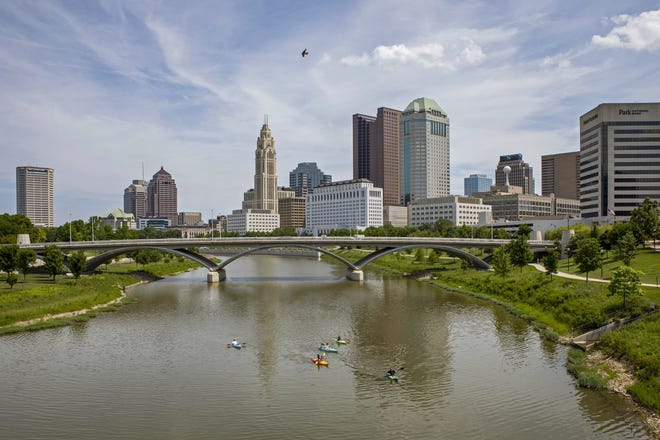 A group of kayakers makes its way down the Scioto River toward the Scioto Mile in Downtown Columbus on July 3, 2020.