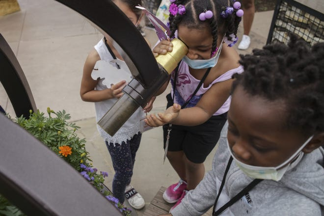 """Onyx Burke, 7, looks through a kaleidoscope at a bouquet of flowers at Franklin Park Conservatory and Botanical Gardens during Columbus City Schools' Summer Experience. She said it was the """"funnest day"""" of her whole life."""