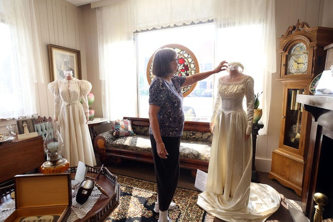 Museum committee member Janet Shailer looks over the bridal gowns on display at the Grove City Welcome Center and Museum, 3378 Park St., on July 21. The bridal-gown exhibit will be on display through Sept. 1.