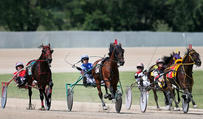 In this file photo, Chris Page, center, drives Always Connected in 2015. Scioto Downs canceled harness racing this week, but races are expected to resume Friday.