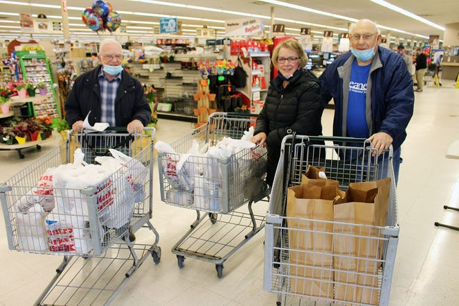 Members of Gleaner Life Insurance Society's Adrian Arbor began a $900 food drive April 23 in Adrian at Country Market, benefiting three Lenawee County food pantries. The group was able to purchase more than $300 worth of groceries for the food bank at Holy Family St. Joseph Catholic Church thanks to a discount by Country Market. From left, Adrian Arbor member Wayne Carpenter, St. Vincent de Paul food pantry representative Melissa Austin and Adrian Arbor vice president Roger Roback pose for a photo with their full grocery carts.