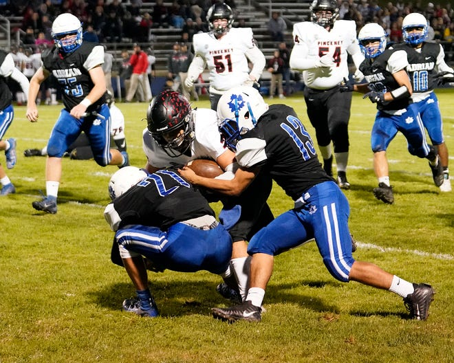 Two Adrian defenders look to tackle a Pinckney running back during a game in the 2019 season.