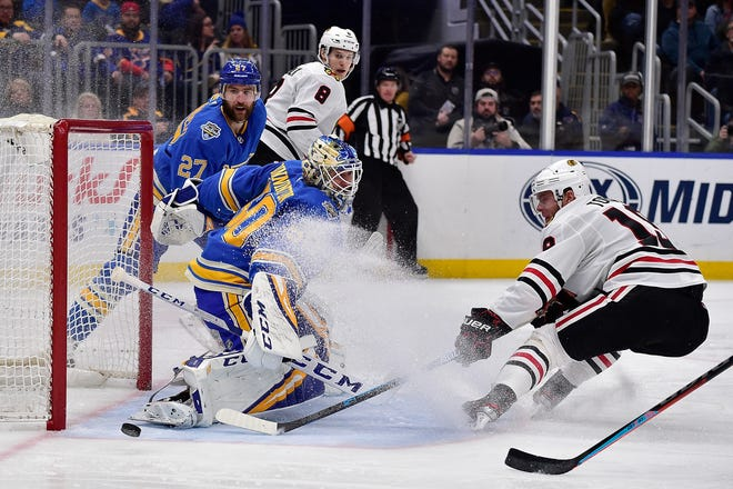 St. Louis Blues goaltender Jordan Binnington (50) makes a save  against Chicago Blackhawks center Jonathan Toews (19) during a 2019 NHL game. The Blues and Blackhawks, longtime rivals, will play a preseason exhibition match on Oct. 2 at Cable Dahmer Arena.