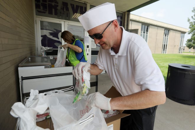 Burlington High School kitchen manager George Houlton fills a bag with several breakfast items Tuesday during the Burlington School District's summer meal program at Burlington High School. Nearly 400 lunches and almost as many breakfasts are being picked up daily at the high school's curbside pickup location from 11 a.m. to 1 p.m. Monday through Friday. All children 18 years of age and younger can receive free meals at several locations and do not have to be enrolled in the Burlington School District.