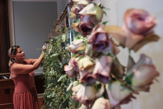 Volunteer Nikki Koren hangs up a string of eucalypti at the Cummer Museum on Monday, July 19, 2021. Volunteers are helping to put together flowers, eucalypti and other plants as a part of an exhibition at the Cummer by Rebecca Louise Law opening on July 30.