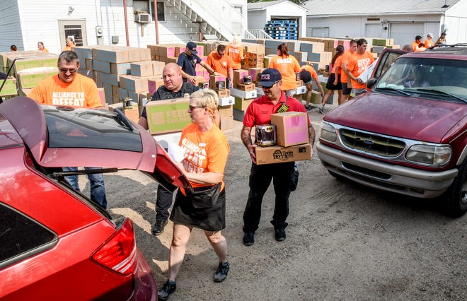 """Volunteers, inluding staff from the Garden City Police Department and Garden City Fire Department, load boxes of food and other products into recipient's vehicles Tuesday at Emmaus House during an """"Alliance to Defeat hunger"""" event by Americold, Tyson Foods and Feed the Children.  Garden City was the only distribution stop in Kansas for the 10-city United States tour."""