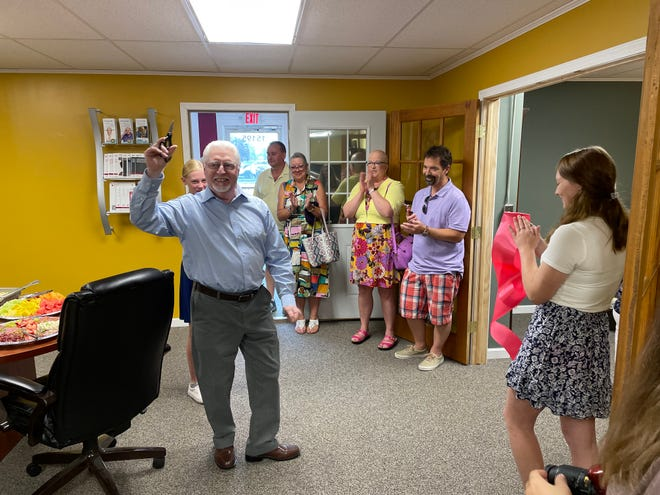 Michael LaHote was all smiles after cutting the ribbon during a ceremony Saturday at Ribbons of Monroe, Inc.