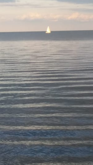 A single sailboat silently floats across Lake Erie's calm waters.